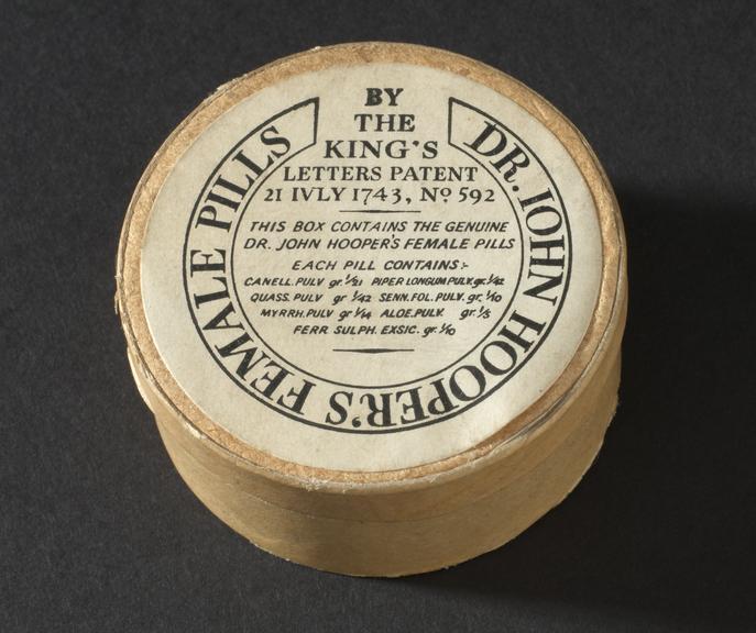 (One of) 2 round pill boxes of Dr John Hooper's Female Pills, by John Hooper, 1900-1950. Top three quarter view. Black