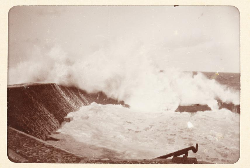 Black and white photograph entitled 'Rocher de la Vierge' showing a view of large waves breaking on the rock, taken by