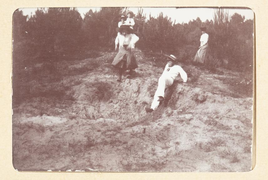 Black and white photograph entitled 'A Long Jump in the Pinewoods'. The photograph shows, from left to right, HH Prince