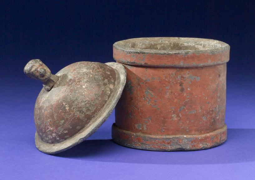 Cylindrical lead tobacco jar, English, 1790-1830. Image of object and object lid; leaning on jar. Blue/black graduated