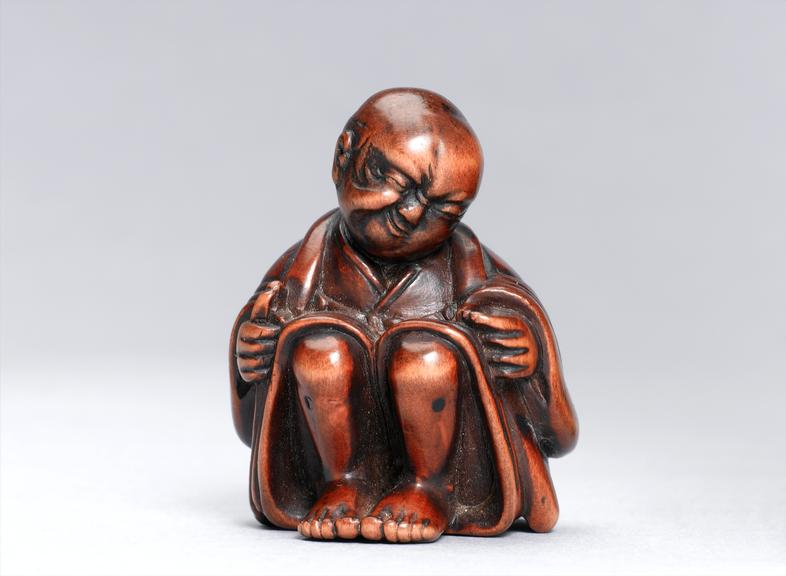 Wooden figure showing moxibustion, Japan, 1700s. Front view. Light grey background.