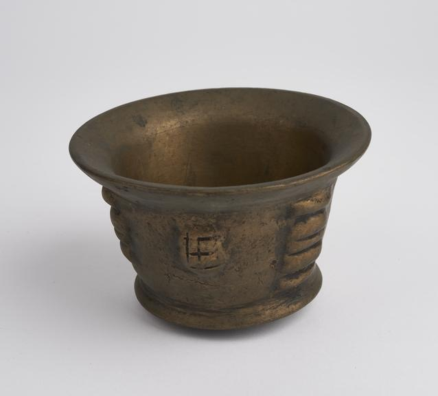 Small brass (?) mortar, flared rim and foot, flat