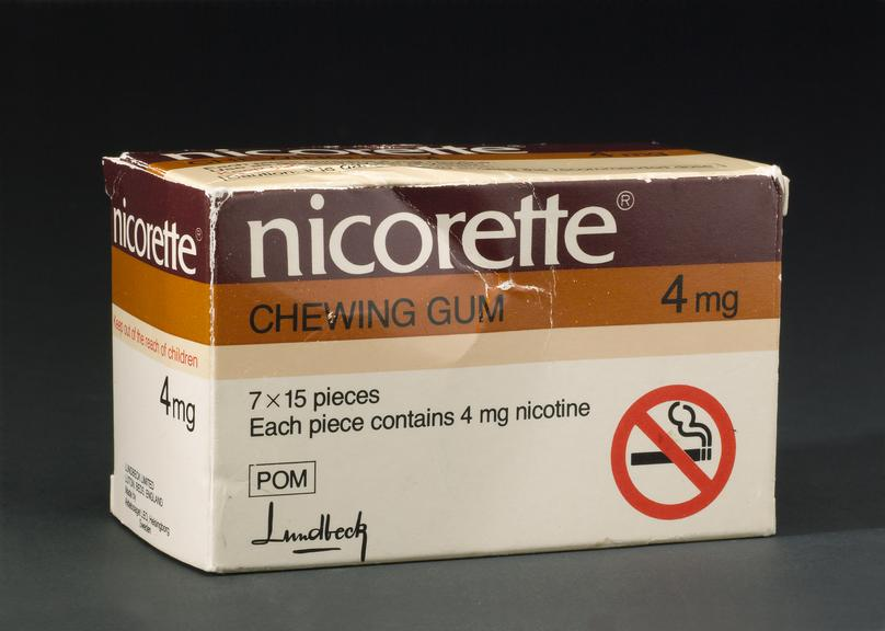 Pack of Nicorette chewing gum, 1984. Front three quarter view. Dark grey background.