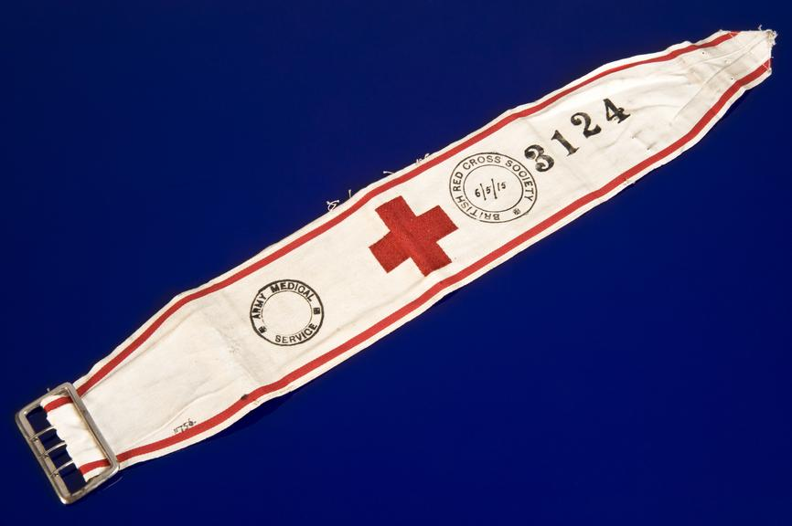 Arm band of British Red Cross Society, 1915.       Full view, blue background.