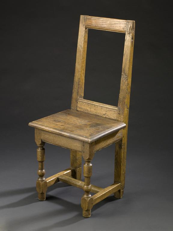 Chair from the Hotel Dieu in Paris, 15th century.  Front 3/4 view of whole object against dark grey graduated background