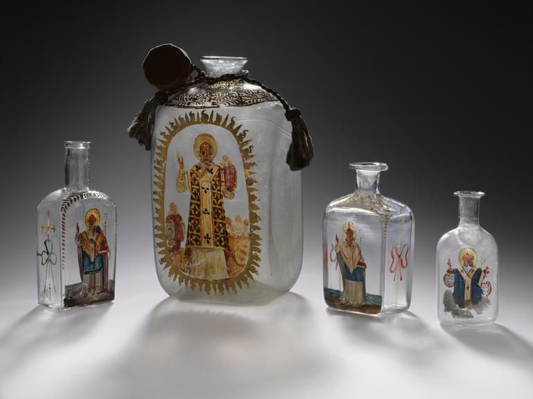 From left to right:       A660480: Glass bottle with Saint, possibly St. Nicholas of Myrna, painted on side, possibly