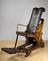 Adjustable dental chair, 18th century.        Full 3/4 view, split grey background.
