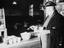 British Rail worker in mess room putting sugar in tea.