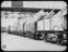 Timber planking loaded onto wagons at yard/port.